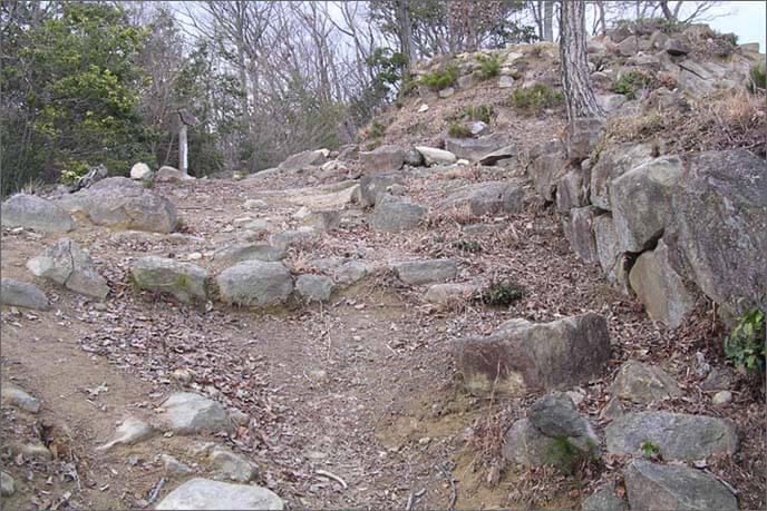 崖に挟まれた曲輪(くるわ)の上の建造物の痕跡を留める礎石